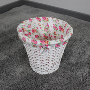 White wicker bin with pink floral lining